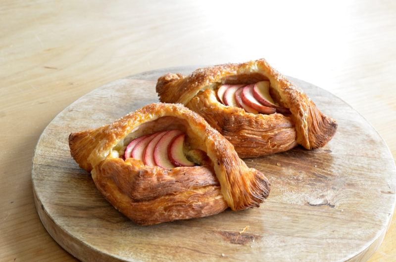 Two diamond shaped Danish pastries filled with sliced apple on a wooden board
