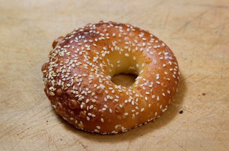 A bagel topped with sesame seeds on a wooden chopping board