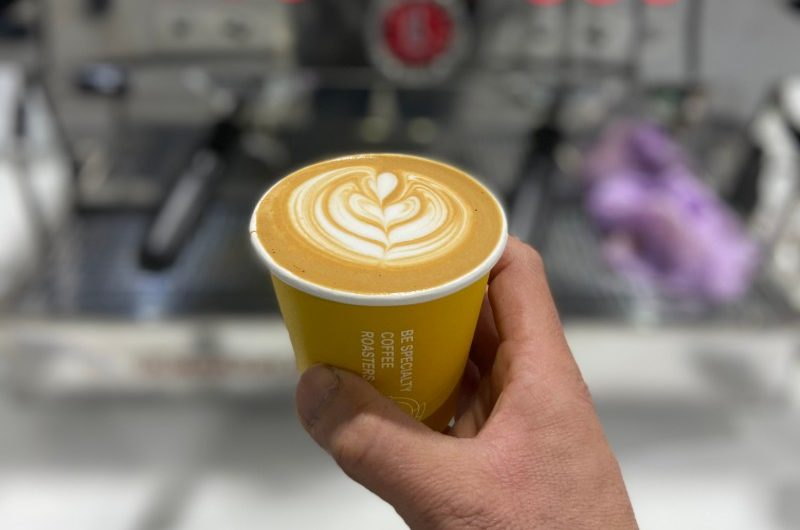 A flat white coffee in a takeaway cup made by BE Specialty