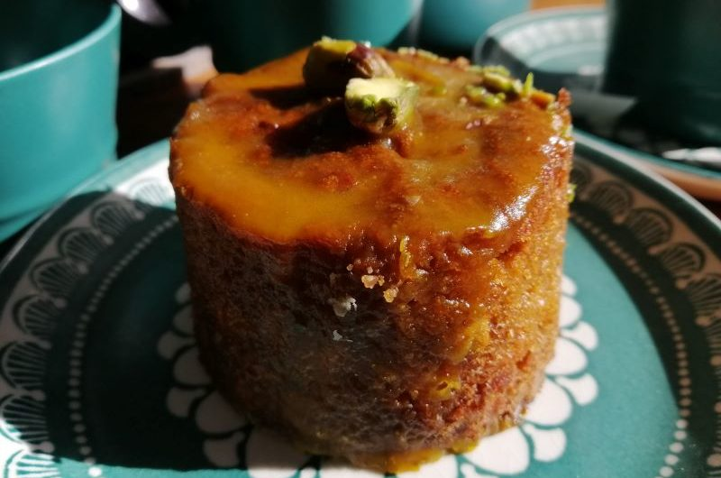 A small round carrot cake smothered in a light caramel glaze with a pistachio on top