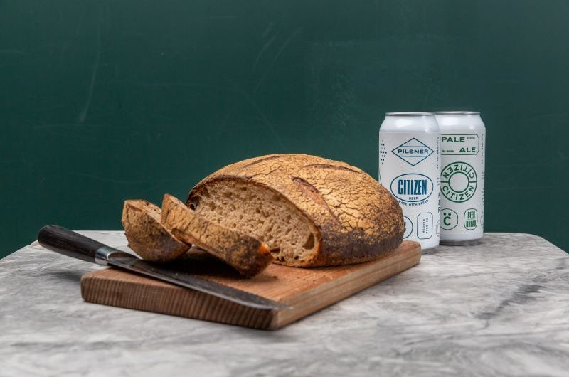A round loaf of sourdough on a chopping board with two slices cut and two cans of beer beside