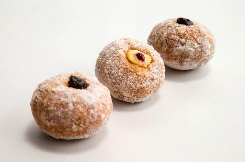 Three round doughnuts filled with chocolate cream, vanilla cream and chocolate cream in a diagonal row