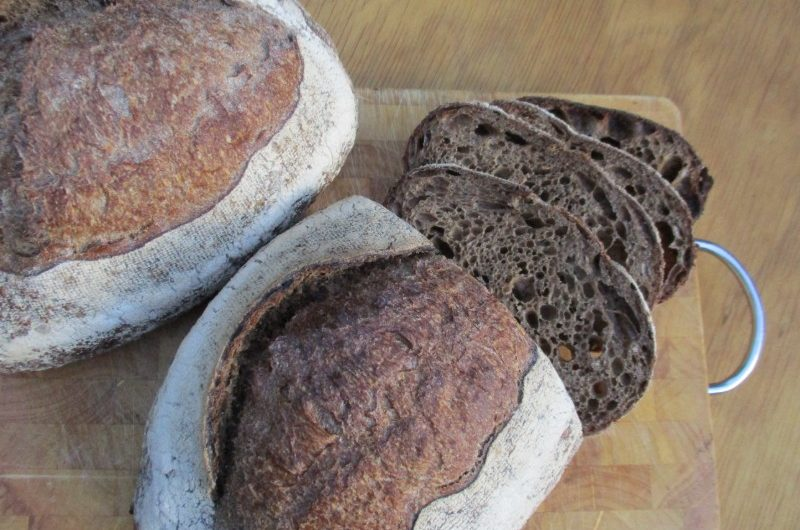 Two loaves of dark rye sourdough with half a loaf cut in slices