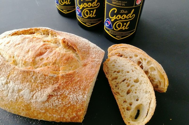 A loaf of Horopito Sourdough with two slices and bottles of The Good Oil in the background