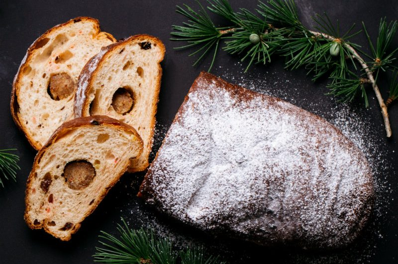 A loaf of German Stollen bread, dusted with icing sugar with three slices where the round marzipan centre is in the middle of each slice