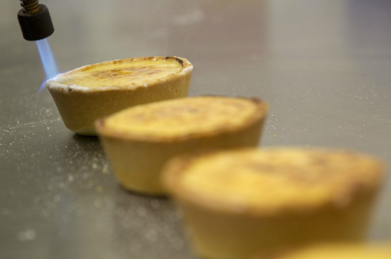 Three brulee tarts in a row, the last one in focus under the blowtorch