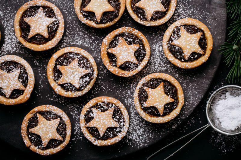 A swag of Christmas Mince Pies with star-cut pastry on top, dusted in icing sugar